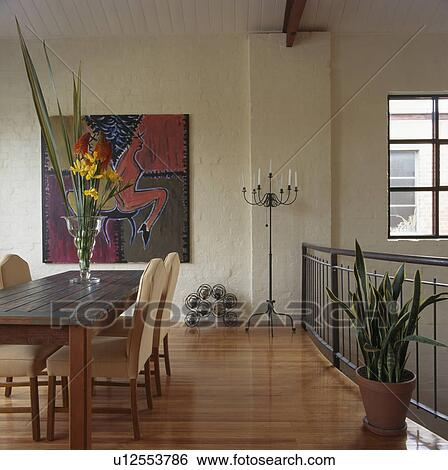 Large Abstract Painting On Wall Of Modern Dining Room With Wooden Floor And Cactus