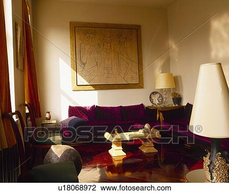 Large picture above dark red sofa in neutral living room ...