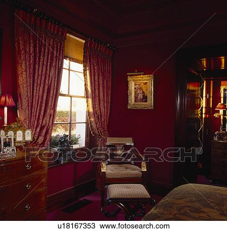 Lighted Picture With Gilt Frame Above Chair And Footstool In Dark Red Bedroom With Patterned Red Curtains And Beige Blind Stock Image U18167353 Fotosearch
