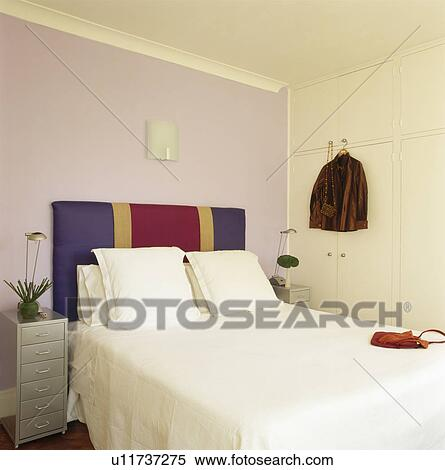 Mauve bedroom with red and blue upholstered headboard and ...