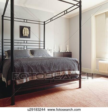 Moderne, noir, métal, lit baldaquin, à, charbon de bois, gris, bedcover,  et, coussins, dans, pâle, gris, chambre à coucher Image