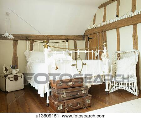 Old leather suitcases below antique white and brass bed in white country  bedroom Stock Image
