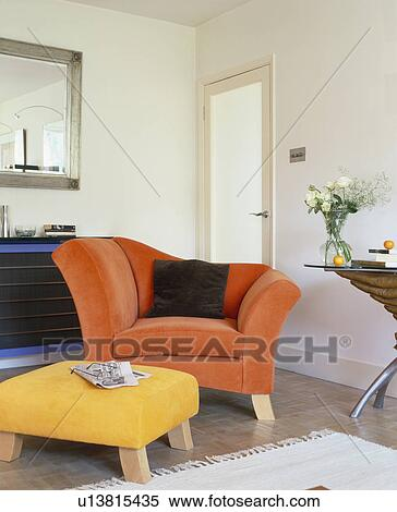 Orange Armchair And Upholstered Yellow Stool In Modern White Living Room
