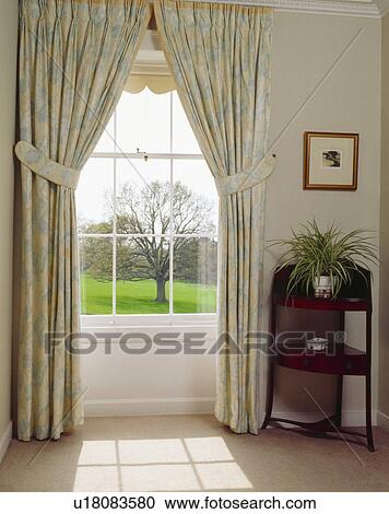 Pastel Curtains At Tall Window With View Of Garden