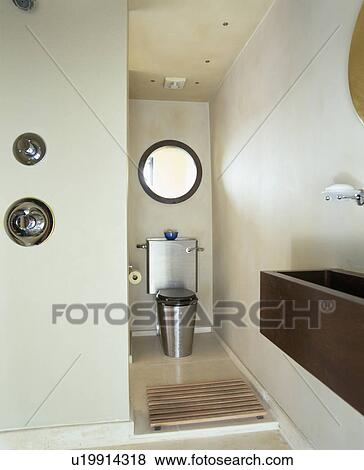 Philippe Starck Stainless Steel Toilet In Modern White Bathroom Stock Photo