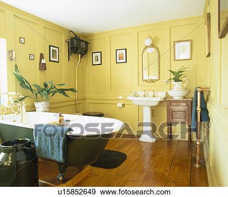 Roll-top, bain, et, blanc, piédestal, bassin, dans, jaune, lambrissé, salle  bains, à, plancher bois Banque de Photo