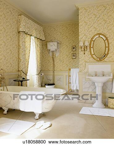 Roll Top Bath And White Pedestal Basin In Country Bathroom With Cream Patterned Wallpaper Matching Curtains