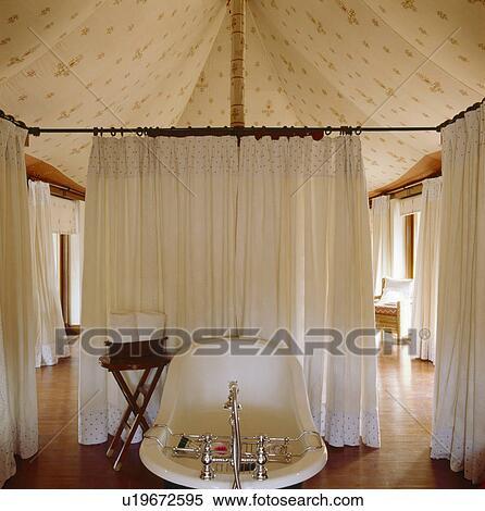 rolltop bad en witte linnen gordijnen in badkamer in rajastani tentje met wooden flooring