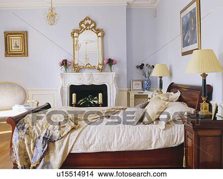 sierlijk verguld spiegel boven openhaard in pastel blauwe slaapkamer