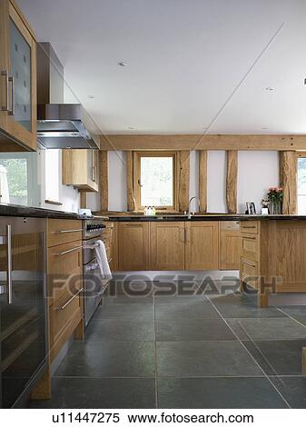 Slate Flooring In Modern White Kitchen With Fitted Wood Units