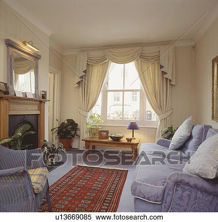 stock afbeelding swagged en tailed room gordijnen in woonkamer met mauve sofa en tapijt en rood oosters tapijt