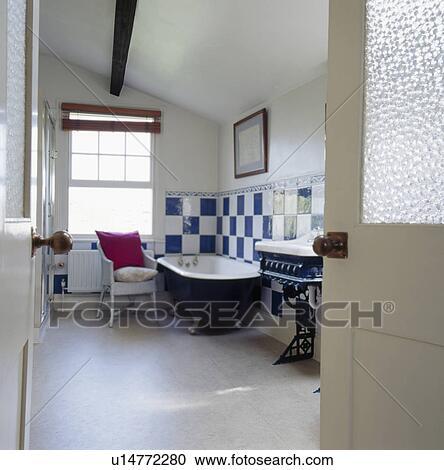 Tür offen, to, dachgeschoss, badezimmer, mit, grauer, keramisch,  fussbodenfliesen, blau, &, weiß, keramische fliesen, oben, rolltop, bad  Stock Bild