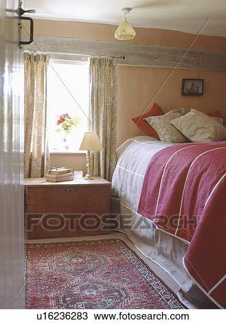 Archivio fotografico torace legno sotto finestra in cottage camera letto con cuscini e - Letto sotto finestra ...