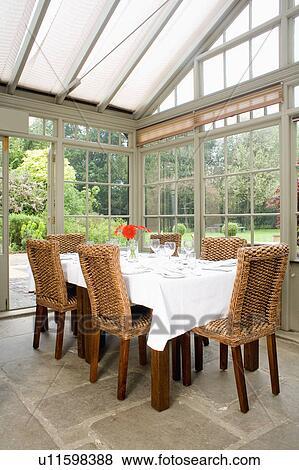 blanco lino tela en tabla en invernadero comedor con mimbre y madera cenar sillas y vista de el jardn