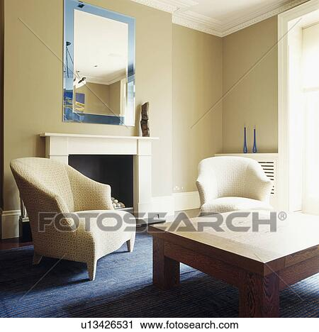 stock fotografie blau glass framed spiegel oben kaminofen in beige wohnzimmer mit. Black Bedroom Furniture Sets. Home Design Ideas