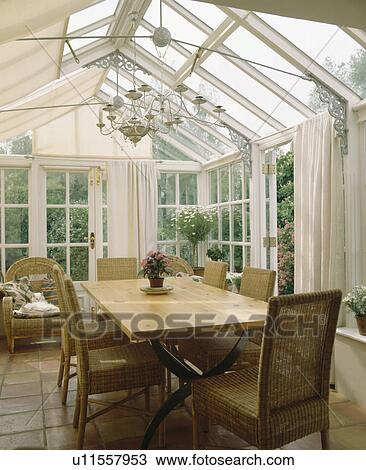 Wicker Chairs And Simple Wooden Table In Traditional Conservatory Dining Room With White Curtains Stock Image U11557953 Fotosearch