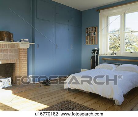 stock foto witte bedlinen op bed in blauwe slaapkamer met wooden flooring