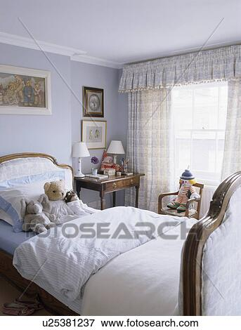 witte bedlinen op upholstered bed in kind pastel blauwe slaapkamer