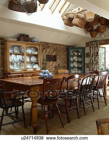 Stock Photo   Wooden Chairs And Long Table In Traditional Dining Room  Extension With Seasgrass Carpet