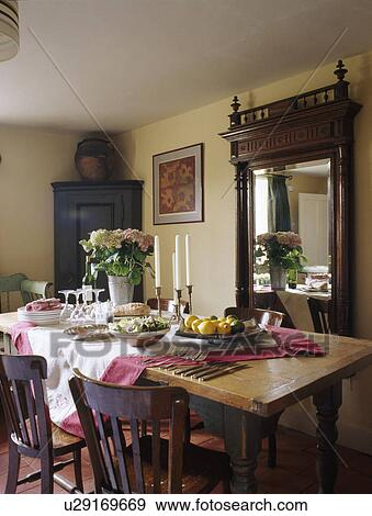 Wooden Table And Chairs In Cream Country Dining Room With Large Antique Mirror Stock Photo U29169669 Fotosearch