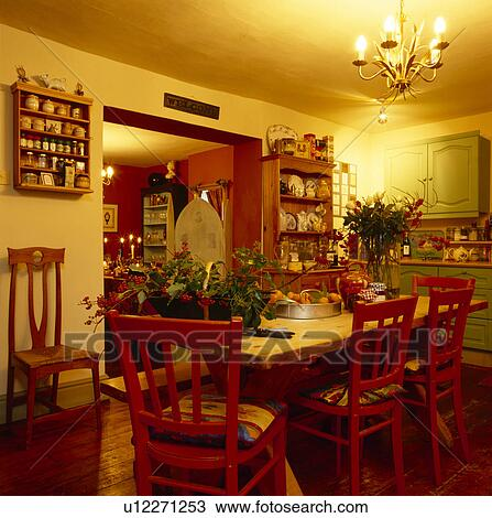 Wooden Table And Painted Red Chairs In Small Yellow Dining Room