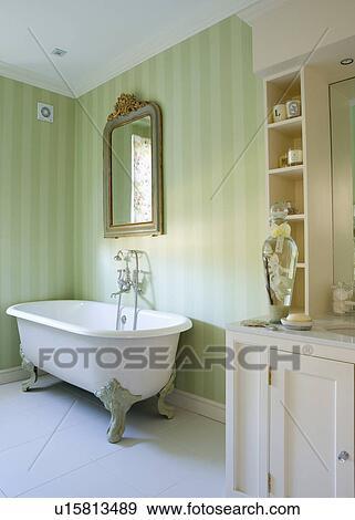 Aufwendig, spiegel, oben, clawfoot, bad, in, traditionelle, badezimmer,  mit, blaß, grün, gestreifte tapete, und, weiß, keramisch, fussbodenfliesen  ...