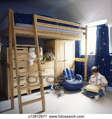 Blue hand shaped armchair and ladder to bunk bed with storage cupboards  below in childrens bedroom Stock Photo