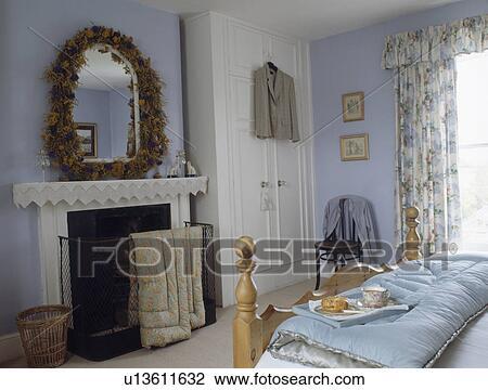 droge bloem guirlande ongeveer spiegel boven openhaard in pastel blauwe land slaapkamer