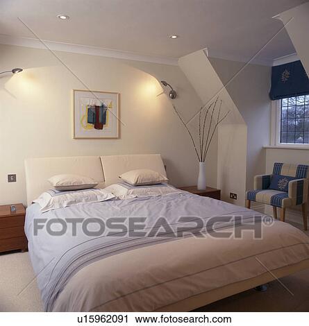 metaal wall lights boven bed met pastel roze en blauw bedlinen in hippe slaapkamer