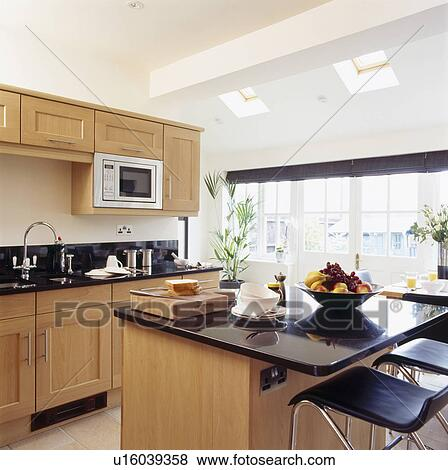Picture Stools At Granite Top Breakfast Bar On Island Unit In Modern Kitchen Extension With