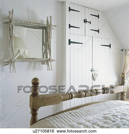 Stock Images of White twig framed mirror in white cottage bedroom ...