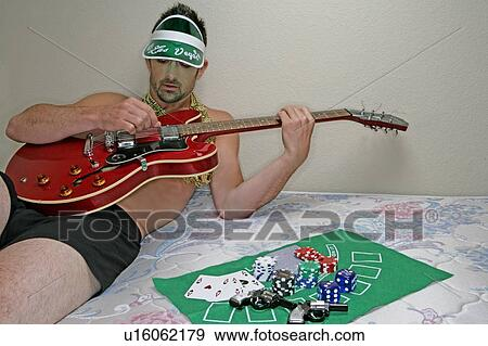 Stock Photograph Of Man Lying On A Bed Playing A Guitar U16062179