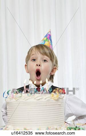 Portrait Of Young Boy Wearing Party Hat Blowing Candles On Birthday