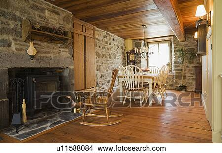 Antique table and chairs in the dining room of an Old Canadiana (1722)  cottage style fieldstone and wooden siding Residential Home, Quebec,  Canada. ...