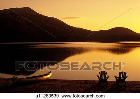 sunrise, lake, Adirondack chairs, Adirondacks, New York, Blue Mountain  Lake, NY, A canoe and two Adirondack chairs on the beach at sunrise on Blue  ...