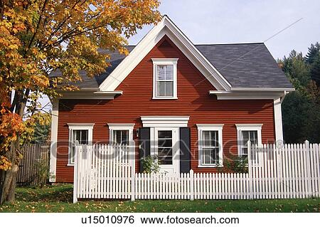 white picket fence. Red Wooden House With White Picket Fence In Autumn