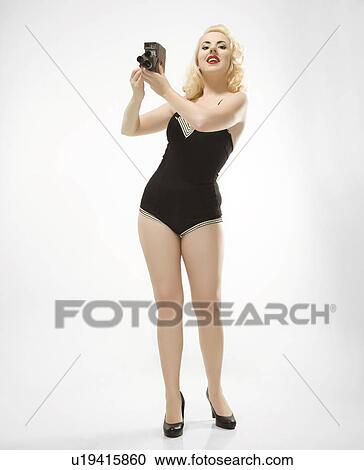fa8ae09a1 Stock Image - Attractive Caucasian woman wearing retro swimsuit in pinup  pose with vintage camera.