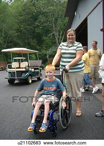 stock photo of boy in wheelchair with woman at camp u21102683