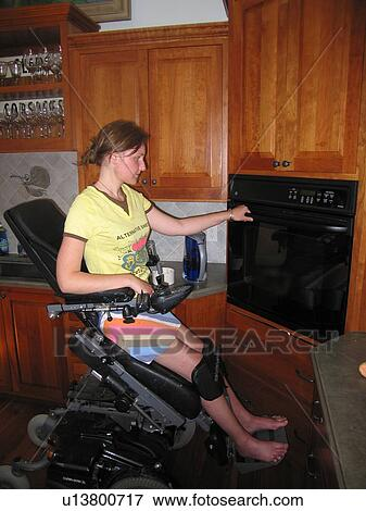 Young Woman Electric Wheelchair User Opens Oven In Her Accessible