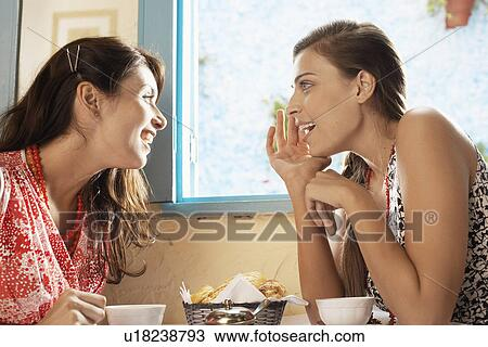 Stock Photo - Two women talking at dining table. Fotosearch - Search Stock  Images 2ec255f6a