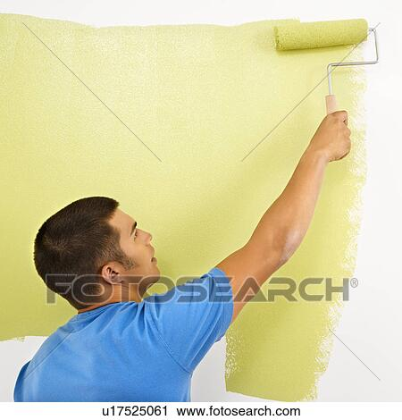 Stock Photography of Man painting over white wall with green paint ...