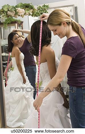 Caucasian Seamstress Measuring African American Bride In Bridal