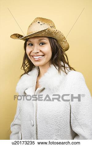 Stock Image - Young adult Caucasian woman wearing cowboy hat smiling at  viewer.. Fotosearch e40d85088e0b
