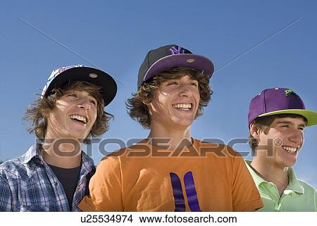 Stock Photo - Teen boys wear baseball hat smiling. Fotosearch - Search  Stock Images e6a06d1bb1f