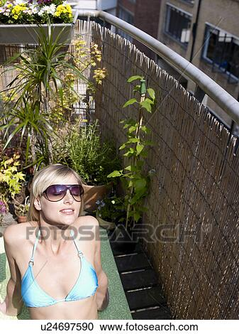 Stock photography of woman sunbathing on city balcony for Balcony sunbathing