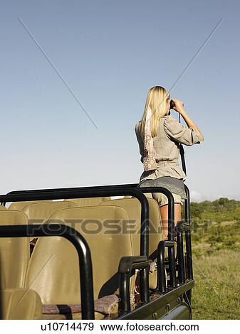 Stock Photograph Of Young Woman On Safari Standing In Jeep Looking