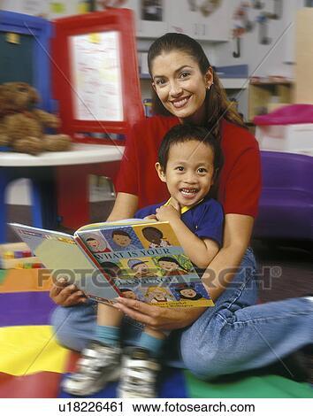Preschool Teacher Reading Language Book With Asian American Boy