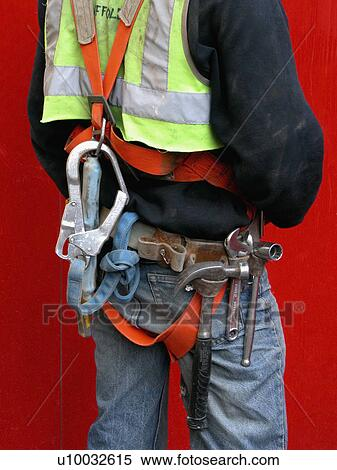 Stock Image of Back view of site worker in safety harness with tool