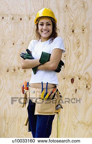 stock photography of young woman on a construction site with hard