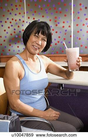 Mature Asian Adult Female Sitting At Table In Health Club Cafeteria